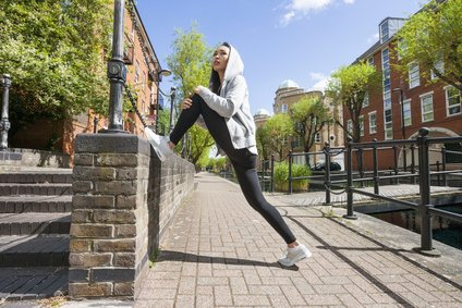 Full length side view of young fit woman stretching on sidewalk