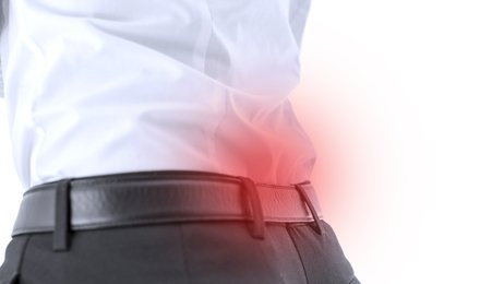 Closeup of male with lower back pain. Red spot emphasizing sore area.